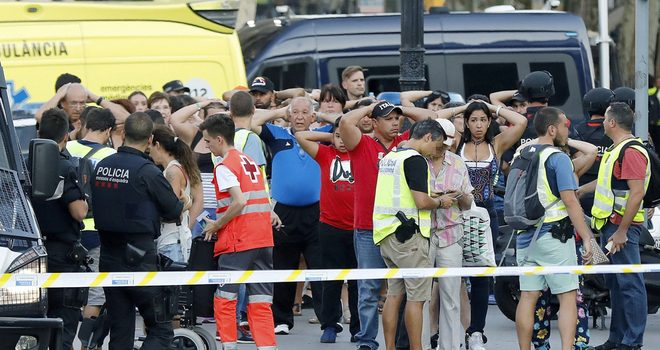 GRA261. BARCELONA, 17/08/2017.- Un grupo de gente con los brazos en alto ante el despliegue policial en el lugar del atentado ocurrido hoy en las Ramblas de Barcelona, un atropello masivo en el que una furgoneta ha arrollado a varios peatones que paseaban por la zona, y en el que un total de 13 personas han fallecido y más de 50 han resultado heridas. EFE/Andreu Dalmau